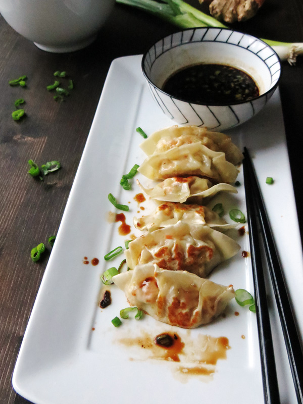 homemade gyozas cooked and sitting on a plate ready to eat