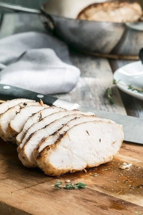 Sliced juicy baked chicken breast on a cutting board