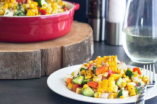 corn salad on a plate with a big bowl of it behind
