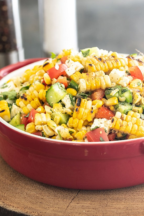 corn salad with feta, peppers and cucumbers tossed in a bowl