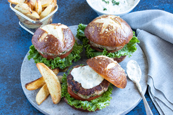 three burgers on a platter with some wedge fries