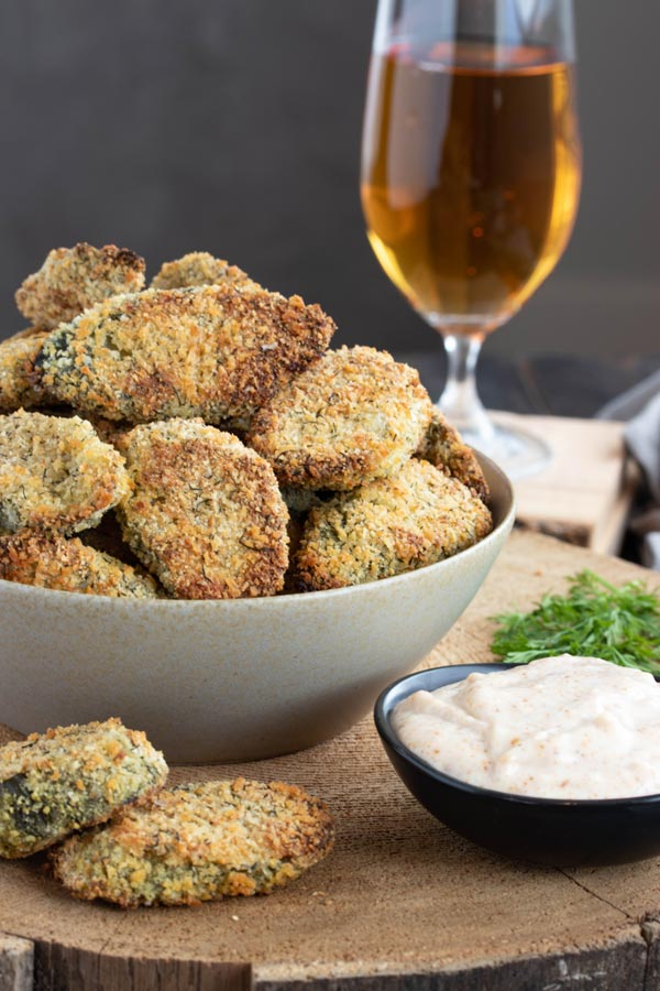 a bowl of oven fried pickles with a beer and some dipping sauce