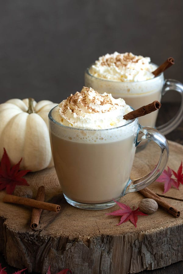 two pumpkin spiced lattes with whipped cream and some cinnamon sticks and nutmeg