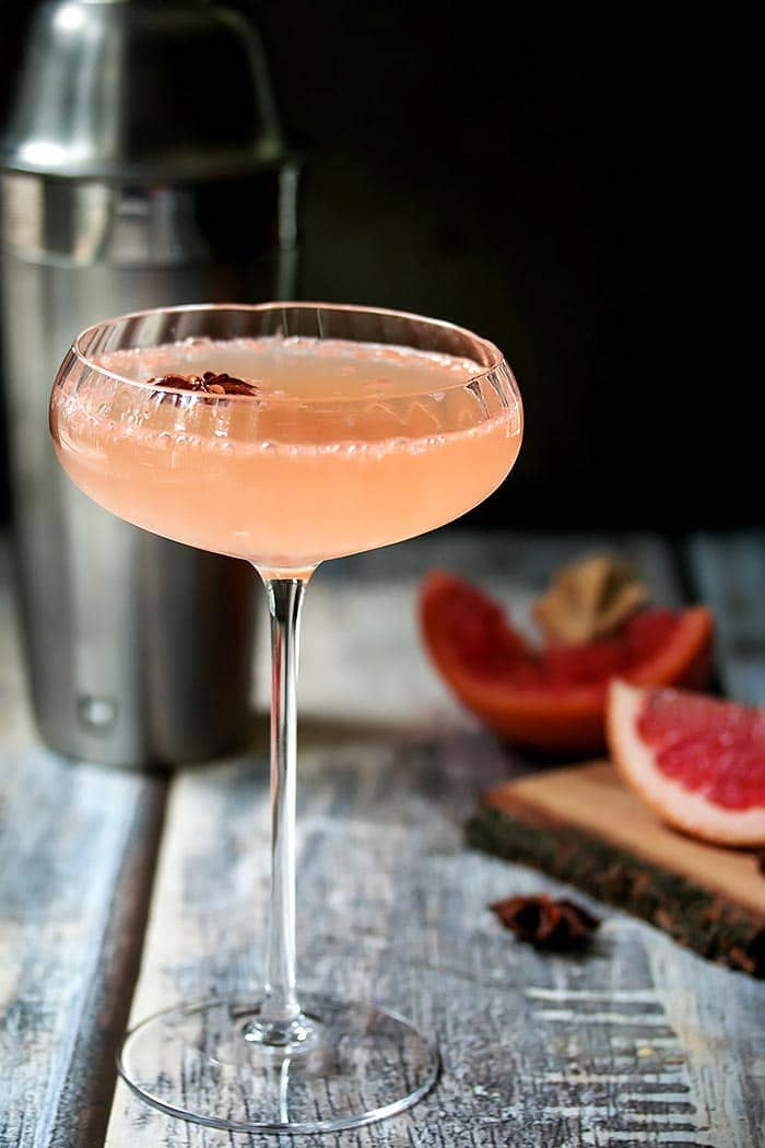 A grapefruit martini made with grapefruit juice, ginger infused simple syrup, lime juice, grated ginger, star anise, rhubarb bitters and a touch of bubbly.
