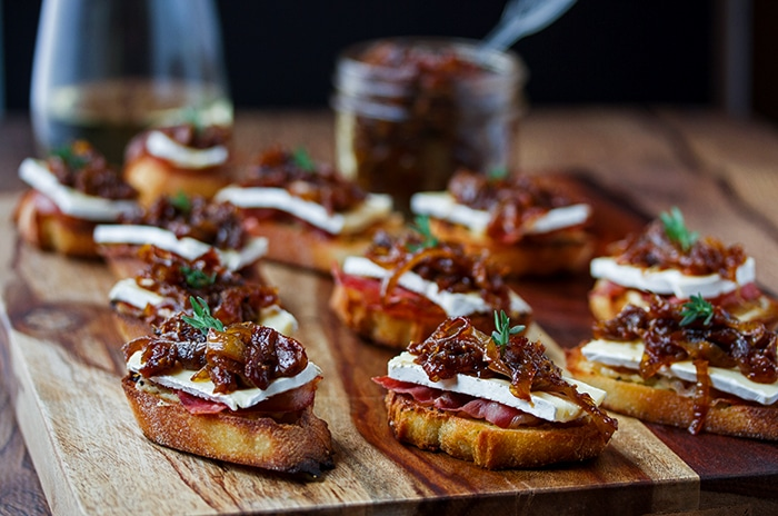 a board of crostinis topped with cheese and fig jam ready to be served to guests