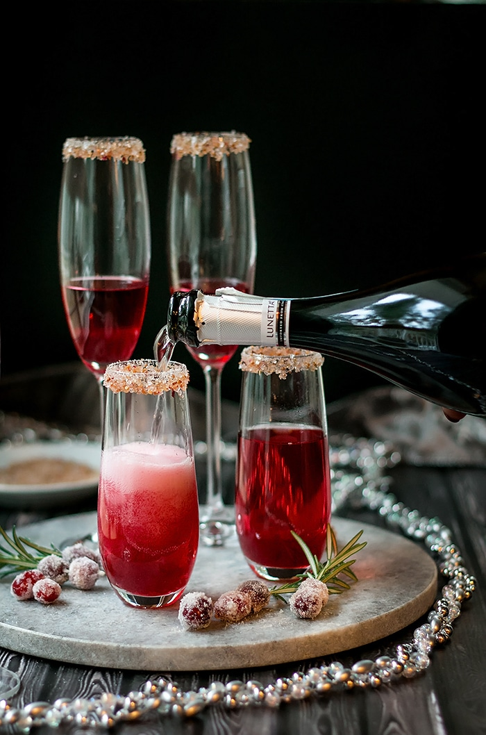 pouring sparkling wine into a short champagne flute with cranberry sauce in it