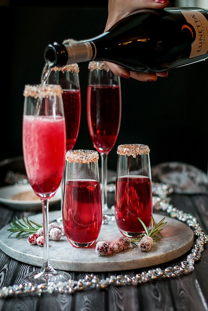 pouring sparkling wine into a tall champagne flute with cranberry sauce