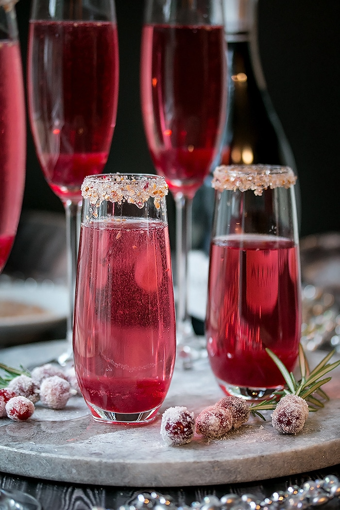two cranberry mimosas with sugared rims. sugar covered cranberries all around