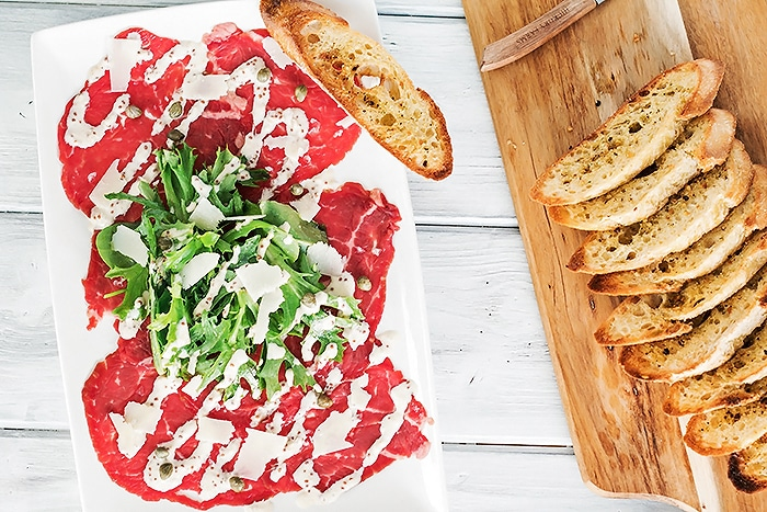 Looking down on a plate of beef carpaccio and crostinis beside it on a cutting board
