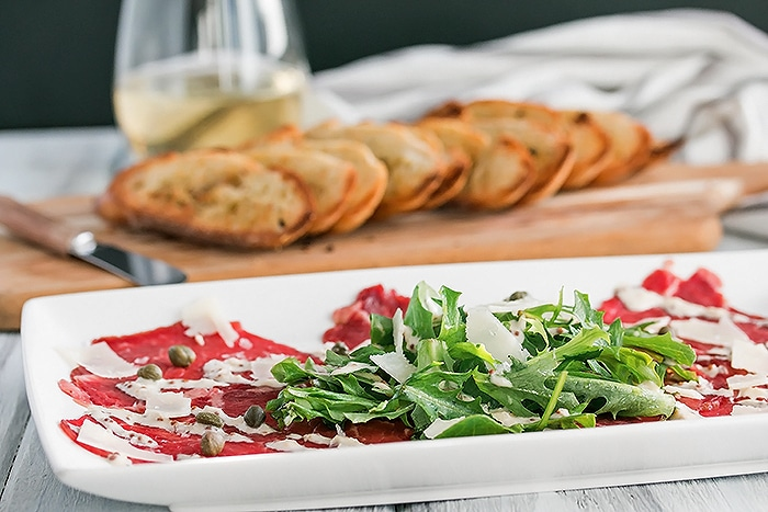 Beef Carpaccio arranged on a rectangle white plate drizzled with sauce and with arugula on top