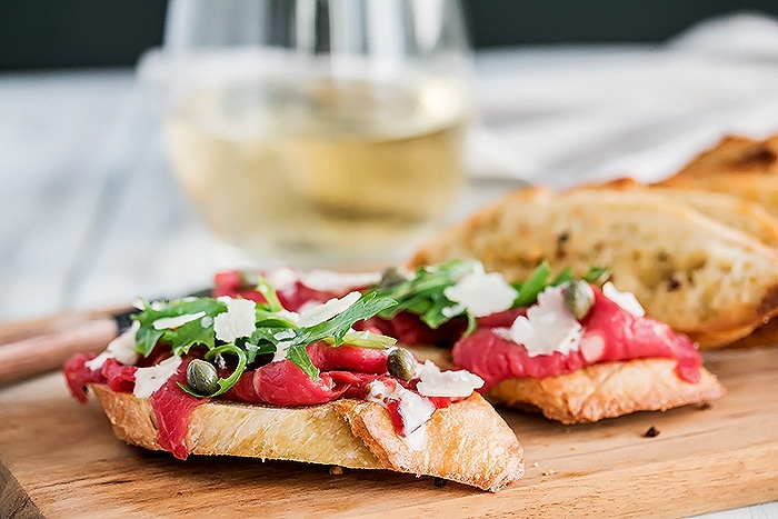 Beef Carpaccio piled on a crostini with parmesan cheese and capers