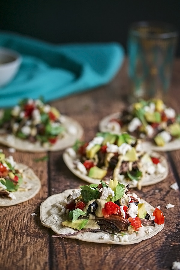 Five Short Rib Tacos on Corn Tortillas with Cheese, Avocado, Tomato and Sour Cream