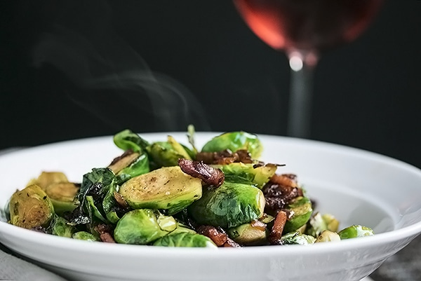 pan fried brussel sprouts with bacon in a serving bowl