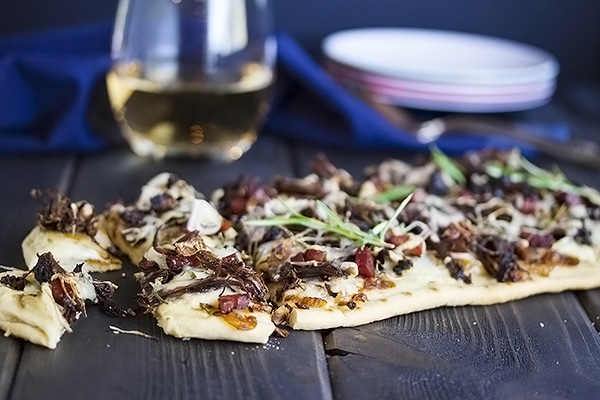short rib flatbread pizza cut into bite sized pieces