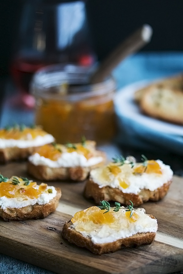 a tray of crostinis with wine jelly on top