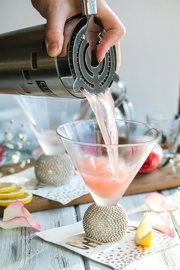 pouring the rose lemon drop martini into a martini glass