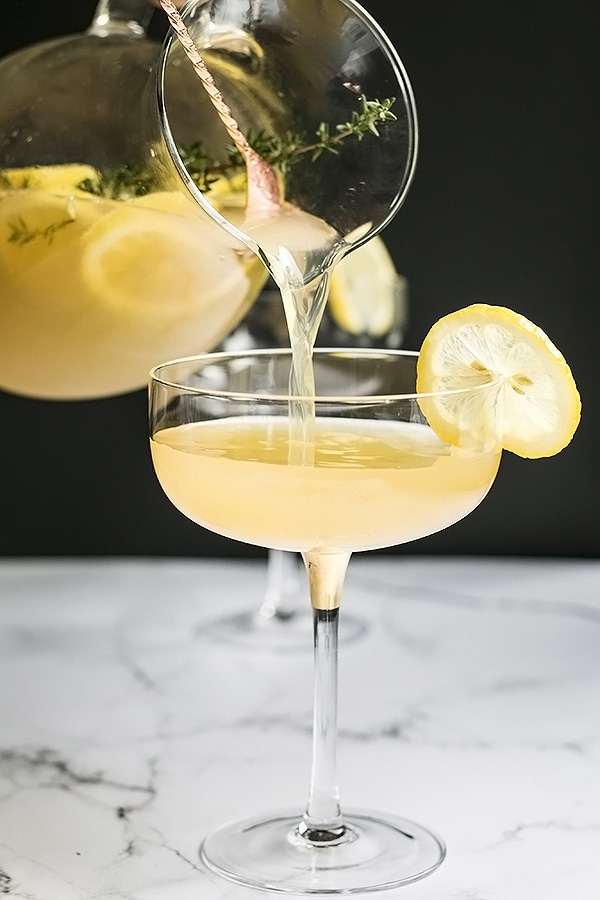 pouring a glass of the bees knees cocktail with tequila and sparkling wine