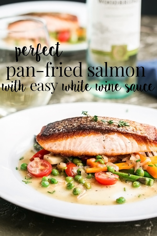 Perfect pan fried salmon with super crispy skin and moist and flaky meat served with tender spring vegetables and an incredibly simple, 2 ingredient white wine sauce. It's WAY easier than you think, ready in about 20 mins (including prep time!) and will be the best salmon you have ever tasted! #cookswithcocktails #panfriedsalmon #crispyskinsalmon #whitewinesauce