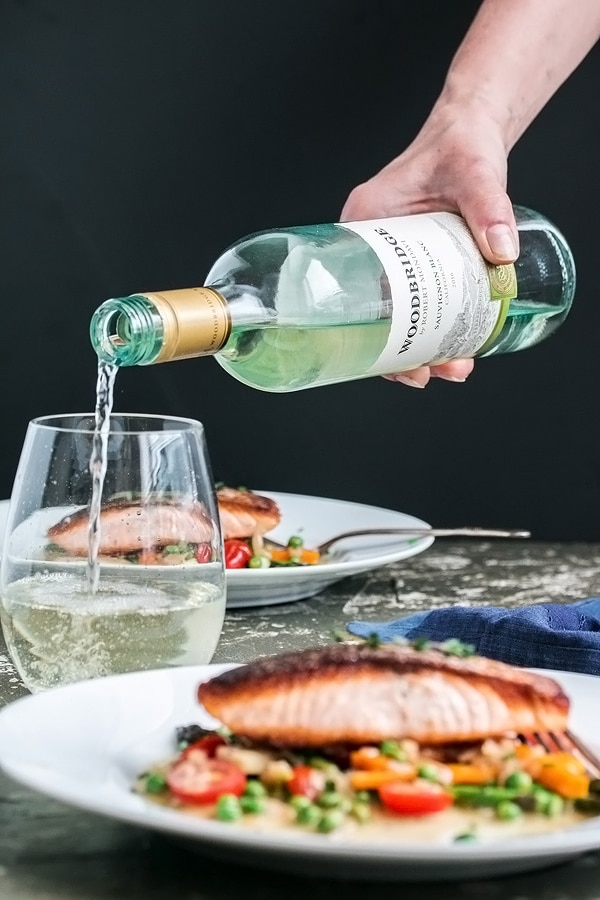 pouring wine for dinner with the plate of pan fried salmon in front of the glass