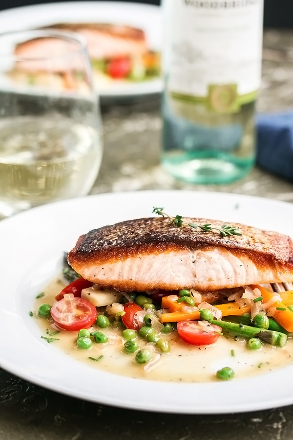 close up view of a piece of pan fried salmon on spring vegetables covered in a white wine and butter sauce