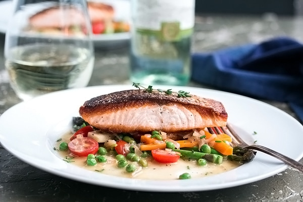 a piece of pan fried salmon on a plate with spring vegetables and a fork