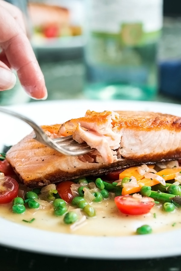 a fork taking a piece of flaky pan fried salmon
