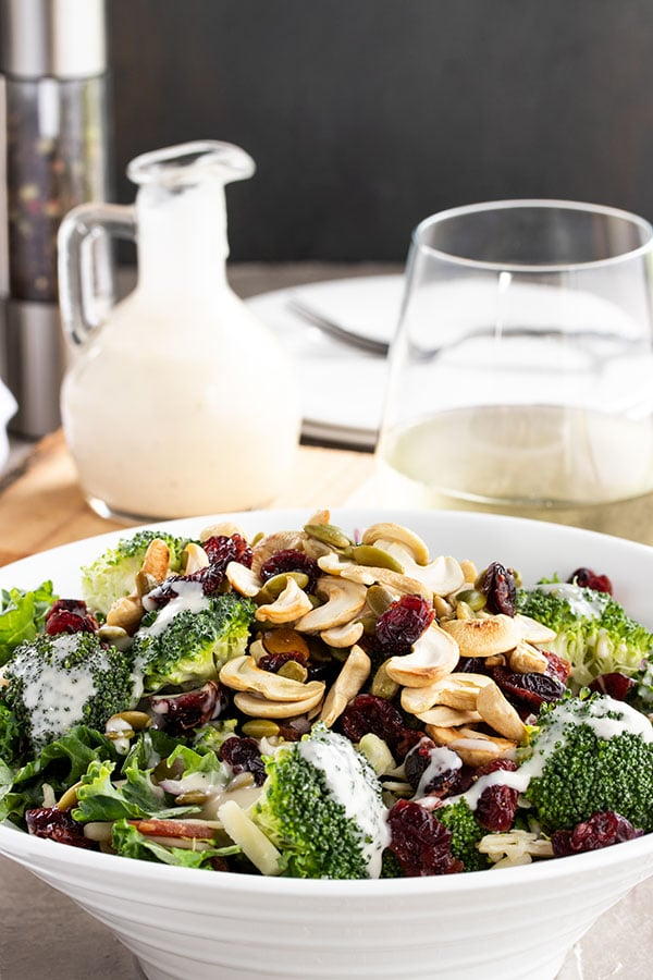 Bowl of broccoli salad with cashews and cranberries on top and ready to serve