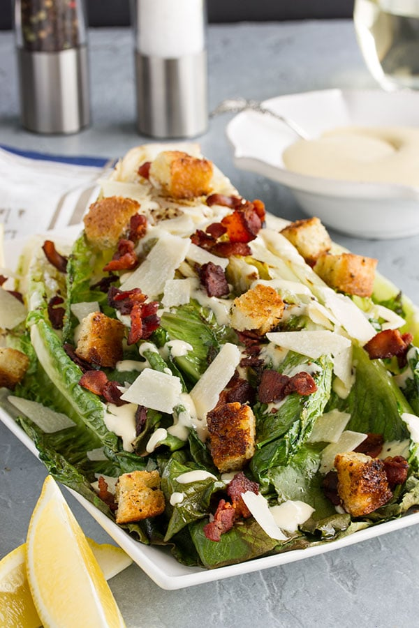 a grilled caesar salad on a plate ready to serve with bacon, croutons, and parmesan cheese
