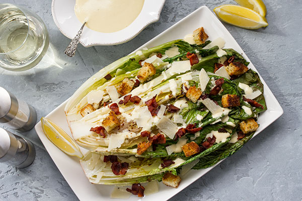 grilled caesar salad on a plate drizzled with caesar dressing
