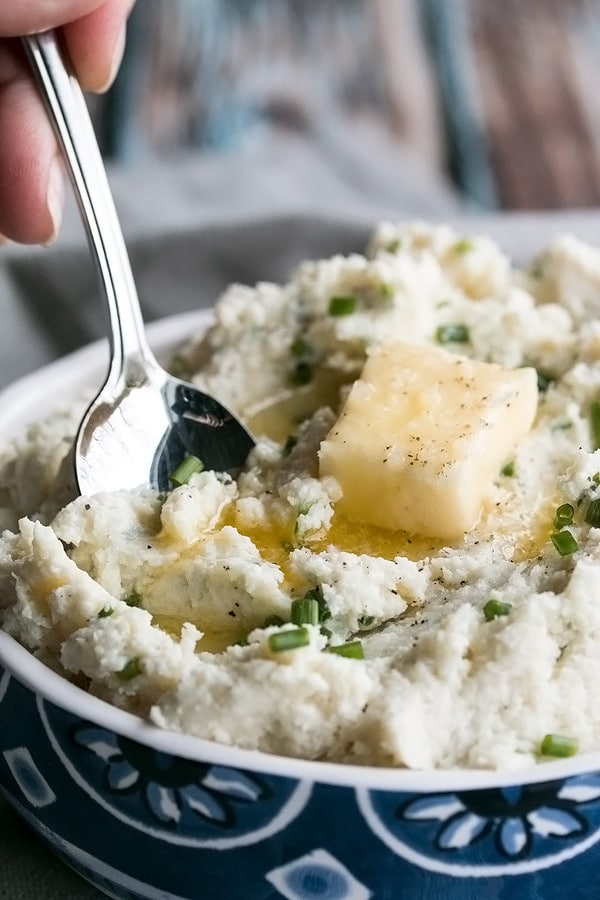 a blue bowl of cauliflower mash with butter melting on it.