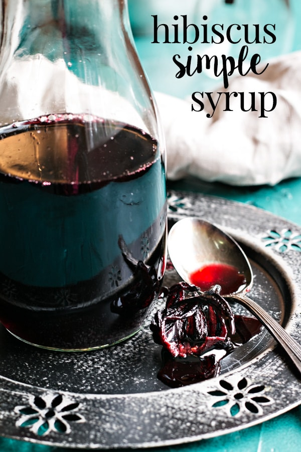 A beautiful dark pink hibiscus syrup that infuses a fragrant floral flavor into cocktails or any drink you mix it in. Its an easy simple syrup with dried hibiscus flowers, that's perfect for creating pretty pink summertime cocktails for sipping with the girls. #cookswithcocktails #hibiscussyrup #driedhibiscusflowers #hibiscuscocktails #floralcocktails