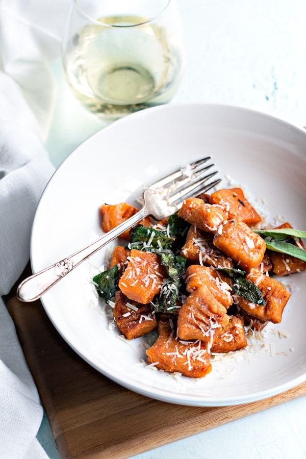 sweet potato homemade gnocchi pan fried and in a white bowl with sage leaves and parmesan cheese
