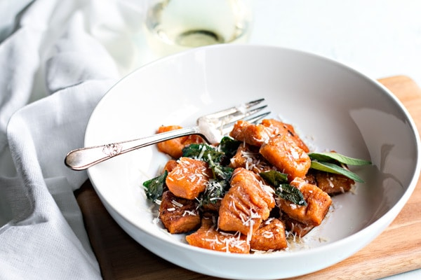 sweet potato gnocchi in a white bowl with a fork and fried sage