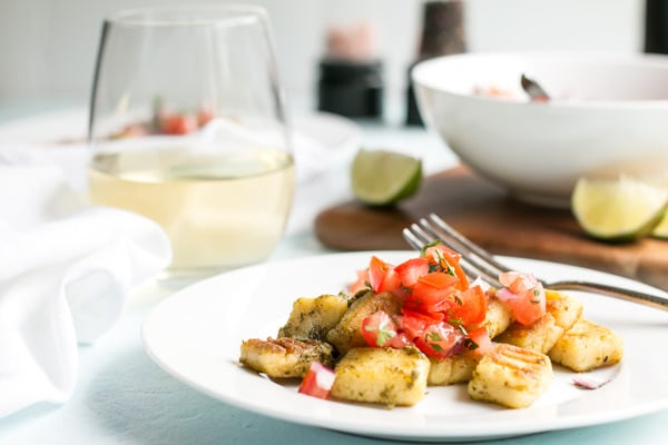 a plate of homemade gnocchi tossed with pesto and topped with pico de gallo