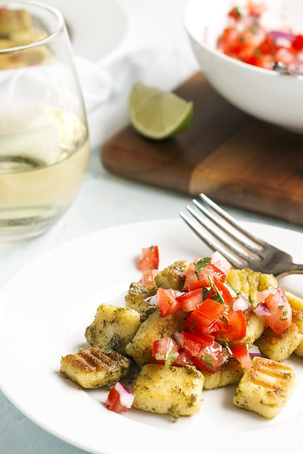 homemade gnocchi with truffled pesto on a white plate and fresh pico de gallo spooned on top