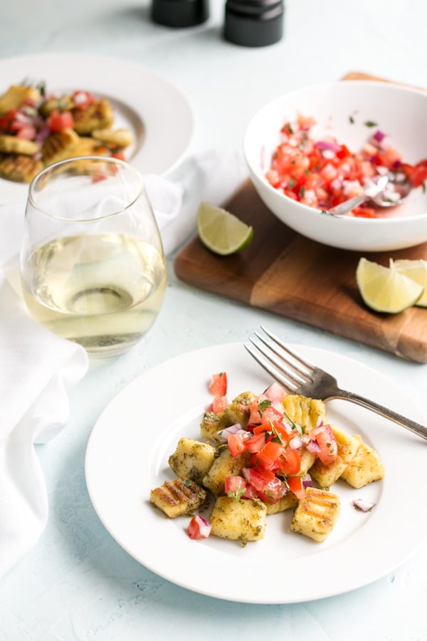 a white plate with homemade gnocchi on it with pico de gallo on top