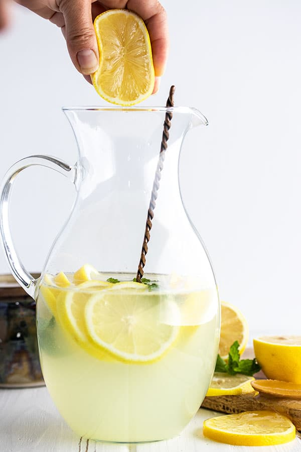 squeezing fresh lemons into a pitcher for homemade lemonade.