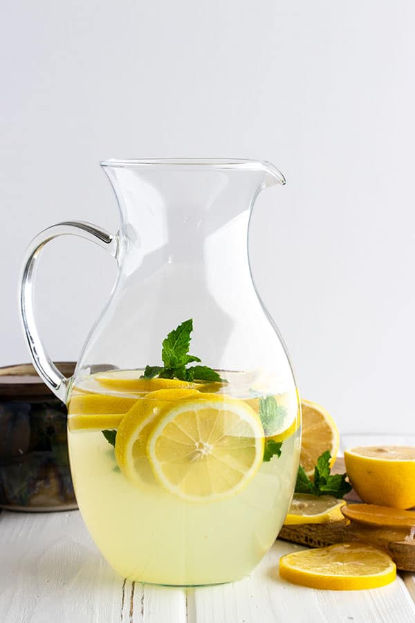 a pitcher full of homemade lemonade with lemon slices and mint floating in it as garnish