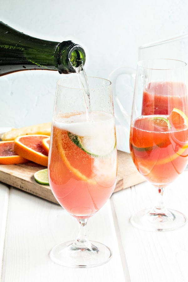 pouring the sparkling wine into the glasses of rum punch