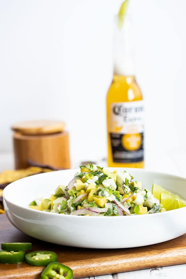 bowl piled high with halibut ceviche with a corona in the background