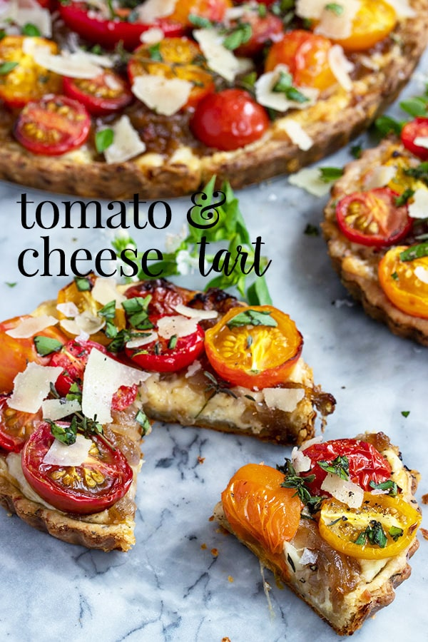 This savory cheese tart is made with three kinds of cheese, fresh baby tomatoes, caramelized shallots and an easy herb and cheddar pastry crust. An easy make ahead tart for entertaining! It can be made as a larger tart or smaller individual mini tarts.  The perfect easy appetizer for a dinner party or a summer appetizer for taking to a bbq. #cookswithcocktails #cheesetart #savorytart #tomatotart