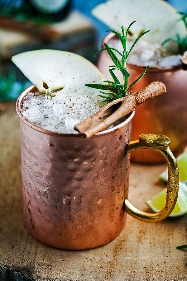a copper mug filled with an apple cider moscow mule, garnished with a stick of cinnamon and a sprig of rosemary