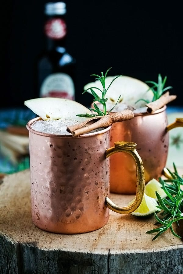 two apple cider moscow mules in a copper cup