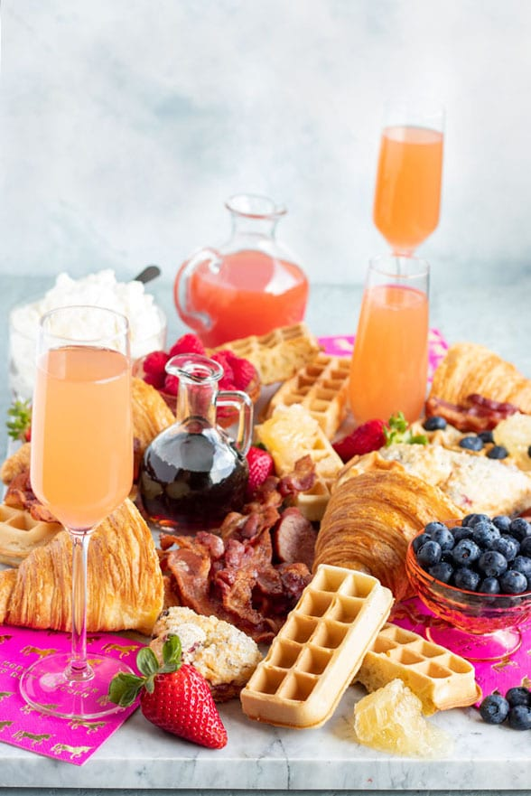a grazing platter with bacon, waffles, fruit, croissants, scones, maple syrup, whipped cream and mimosas!