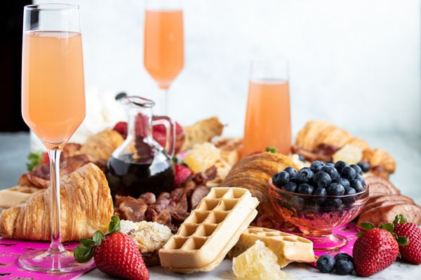 a brunch grazing platter with three grapefruit mimosas, blueberries, maple syrup and waffles