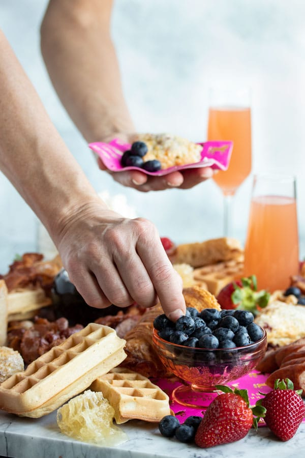A hand reaching for a blueberry on the grazing platter