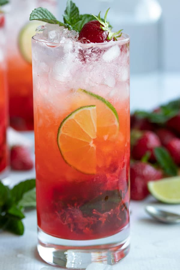 A single strawberry mojito with lime wedges and a strawberry on top!