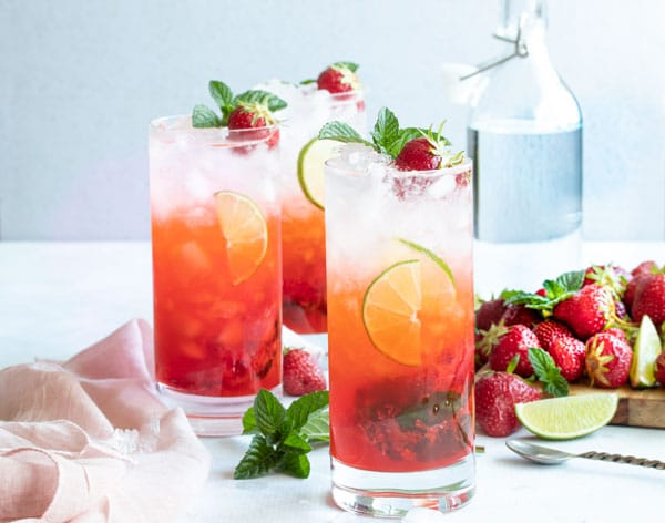 three strawberry mojitos and a bunch of juicy strawberries