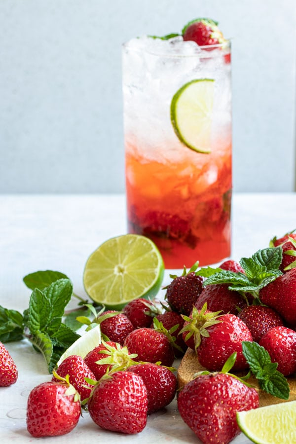 a bunch of juicy strawberries rolling off a cutting board with a mojito in the background