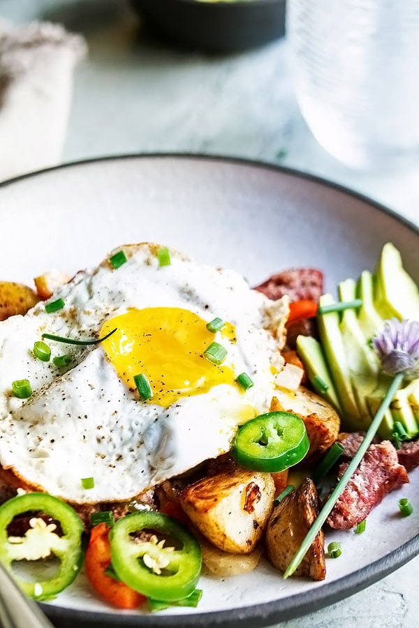 breakfast hash on a plate with an egg on top